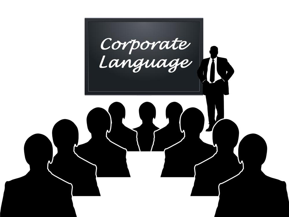 """Silhouetten blicken auf eine Tafel, auf der """"Corporate Language"""" steht. Daneben steht ein Redner mit Anzug."""