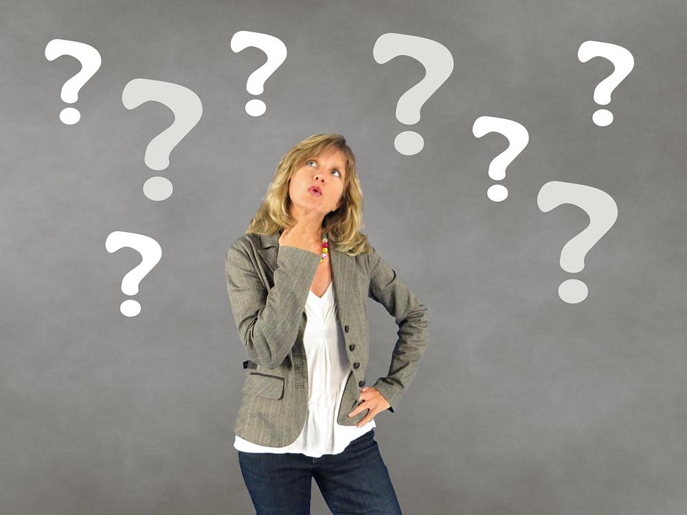 Fragend schauende Frau, um die Fragezeichen schweben.